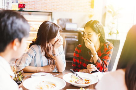 Foto de Two young and cute Asian women talking and laughing together during lunch time - Imagen libre de derechos