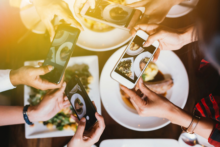 Foto de Group of friends going out and taking a photo of Italian food together with mobile phone - Imagen libre de derechos