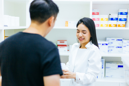 Photo for Asian female pharmacist doctor in professional gown explaining and giving advice with male client in drugstore shop - Royalty Free Image