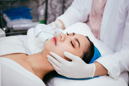 Photo for Young Asian woman getting IPL and laser treatment by beautician at beauty clinic - Royalty Free Image
