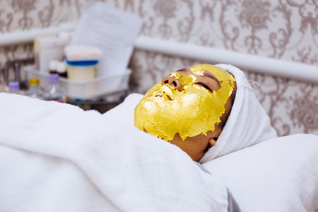 Photo pour Young woman getting 24 karat gold facial treatment at the beauty clinic. The treatment of using real gold for youthful skin - image libre de droit