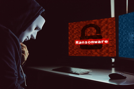 Photo pour Masked hacker under hood using computer to hack into system and employ ransomware - internet computer crime concept - image libre de droit