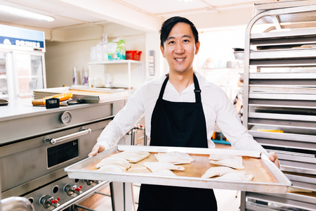 Foto de Young Asian male bakery shop chef smiling and looking at the camera while holding a tray of breads in kitchen in bakery shop scene - Imagen libre de derechos