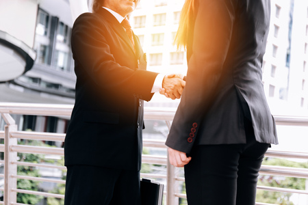 Photo for Professional business woman and man in formal suit shaking hands in outdoor city buildings - Closing deal and business cooperation concept - Royalty Free Image