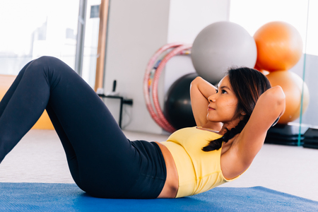 Photo pour Close-up of young active and fitness Asian woman doing sit ups and crunches inside gym with exercise ball in background - image libre de droit