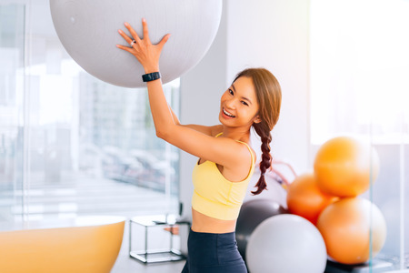 Photo pour Portrait of young fit Asian woman holding exercise swiss ball and smiling at camera. Lively female fitness model image - image libre de droit