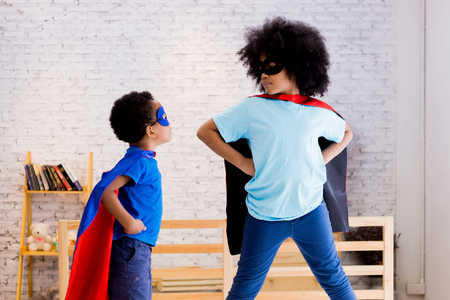 Photo pour African American happy and confident young kids playing   and dressing up as superhero together in bedroom - image libre de droit