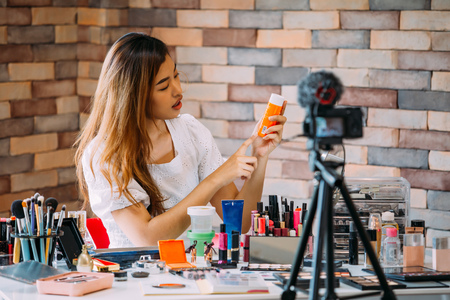 Photo pour Charming Asian girl recording vlog. Beauty blogger presenting makeup cosmetics in front of camera - image libre de droit