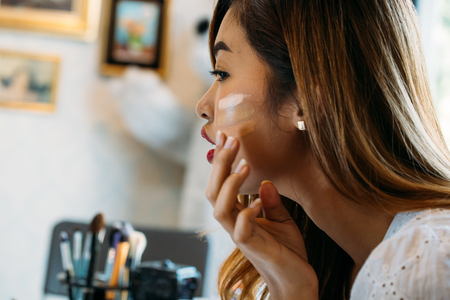 Foto de Closeup young Asian woman with red lips applying corrector on face on blurred background - Imagen libre de derechos