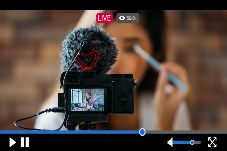 Photo pour Young beautiful woman recording live stream video for makeup and cosmetics business purpose online with video player interface - image libre de droit