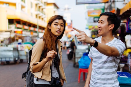 Photo pour Young female tourist asking for directions and help from local people in Bangkok, Thailand - image libre de droit