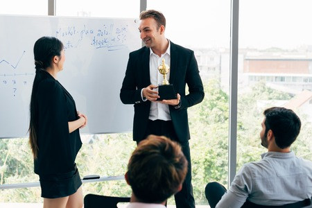 Photo pour Cheerful Caucasian businessman giving award to female employee in front of colleagues during seminar in meeting room of modern office - image libre de droit