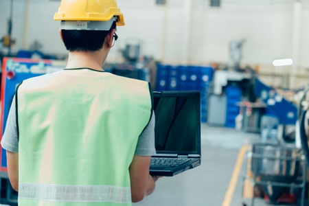 Foto de Asian male Industrial engineer in hardhat works with laptop in safety jacket at heavy industry factory. Processing plastic injection molding industry - Imagen libre de derechos