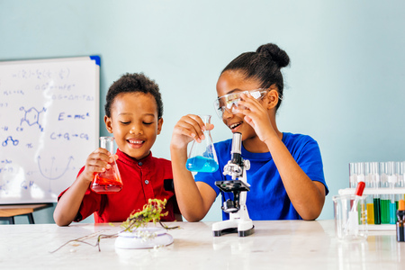 Foto de Two African American mixed kids tests chemistry lab and holding glass tube flask with microscope and smile in science classroom - fun learning concept - Imagen libre de derechos