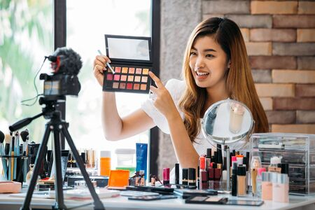 Photo for Pretty Asian woman sitting at table and making video about cosmetics while filming with camera on tripod - Royalty Free Image