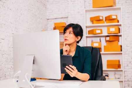 Photo pour Asian entrepreneur with tablet looking away and thinking while sitting at desk in office of e commerce company - image libre de droit
