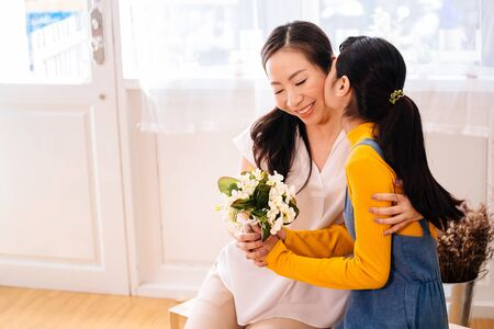 Foto de Face of Asian teenage daughter hugging and kissing happy smiling middle-aged mother with tenderness in indoor living room at home. Mother is holding a bouquet received from child. Mothers day concept - Imagen libre de derechos