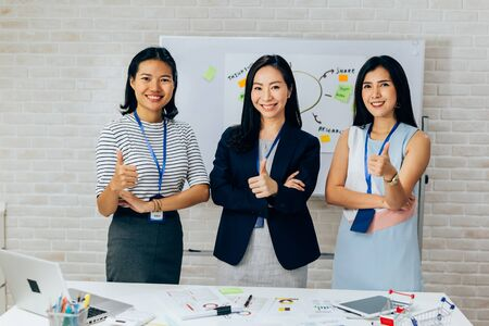 Photo for Smiling Asian young business women in casual wear standing in line with thumbs up gesture in meeting room. Row of Business men and women looking at camera - Royalty Free Image