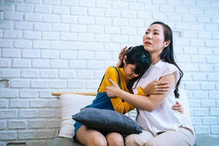 Foto de Asian mother comforting crying teenage daughter in miserable, stressed, depressed, sad state of mind. 40s Mom is hugging this adolescent teenager shoulders at indoors room. - Imagen libre de derechos