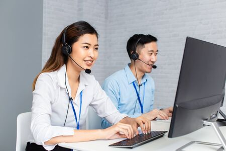 Photo for Cheerful Asian man and woman in headsets smiling and typing on computer keyboard while working in office of call center - Royalty Free Image