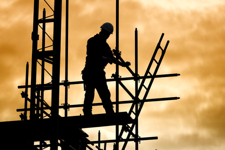 Photo pour silhouette of construction worker against sky on scaffolding with ladder on building site at sunset - image libre de droit