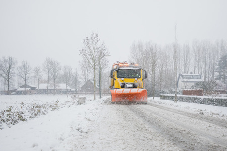 Photo for Snowplow removes snow off icy road in winter - Royalty Free Image
