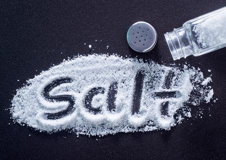 Photo pour white sea salt in bottle and on a table - image libre de droit