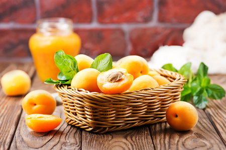 Photo for fresh apricots in basket and on a table - Royalty Free Image