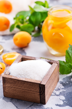 Photo pour sugar and apricots on a table, ingredients for cooking jam - image libre de droit