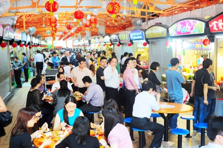 Photo pour Singapore, Republic of Singapore - March 06, 2013: Locals eat at a popular food hall in  Singapore. Inexpensive food stalls are numerous in the city so most Singaporeans dine out at least once a day. - image libre de droit