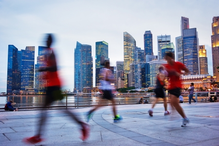 Photo pour People runing in the evening in Singapore - image libre de droit