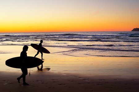 Foto de Two surfer running on the beach at sunset. Portugal has one of the best surfing scenes in Europe - Imagen libre de derechos