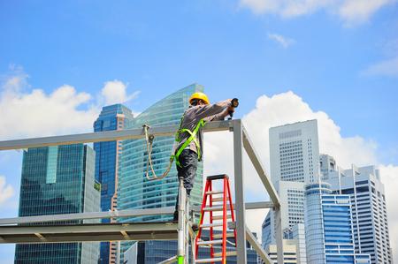 Photo pour Worker at construction site in front of Singapore downtown - image libre de droit