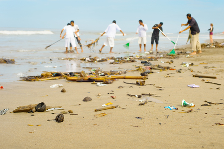 Photo pour People cleaning trashy polluted with garbage ocean beach. Bali island, Indonesia - image libre de droit