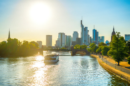 Foto de Sunshine evening, touristic boat at Main river, Frankfurt skyline of modern architecture and people walking by embankment, Germany - Imagen libre de derechos