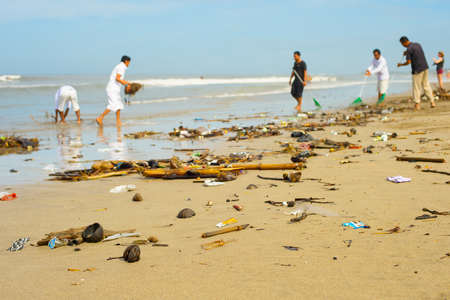Photo pour Group of people cleaning up beach from the garbage and plastic waste. - image libre de droit