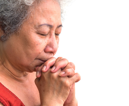 Old woman praying on white background