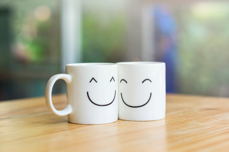 Photo pour Two happy cups on the wood table, about love concept - image libre de droit
