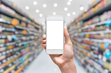 Photo pour Female hand holding mobile smart phone on supermarket blur background, business concept - image libre de droit