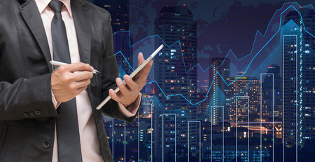 Photo pour Businessman using the tablet on Trading graph on the cityscape at night and world map background,Business financial concept - image libre de droit