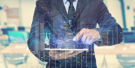 Foto de Double exposure of businessman using the tablet with cityscape and financial graph which have earth and world map on computer blurred background - Imagen libre de derechos