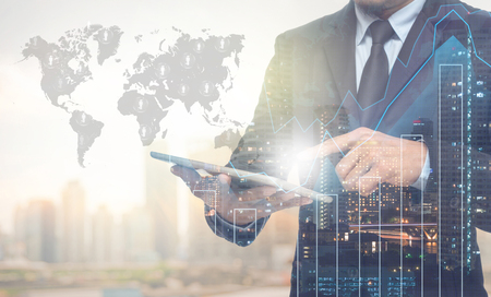 Foto de Double exposure of businessman using the tablet with cityscape and financial graph on blurred building with world map and people logo background, Elements of this image furnished by NASA - Imagen libre de derechos