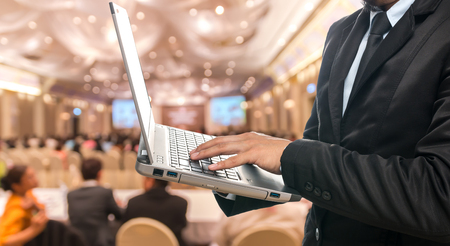 Foto de Businessman using the laptop on the Abstract blurred photo of conference hall or seminar room with attendee background - Imagen libre de derechos