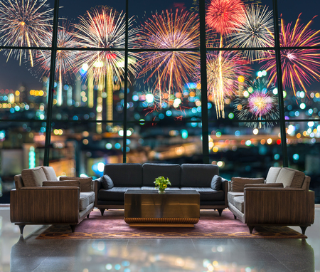 Photo for Lobby area of a hotel which can see Fantastic festive new years colorful fireworks on cityscape blurred photo bokeh in celebration night - Royalty Free Image