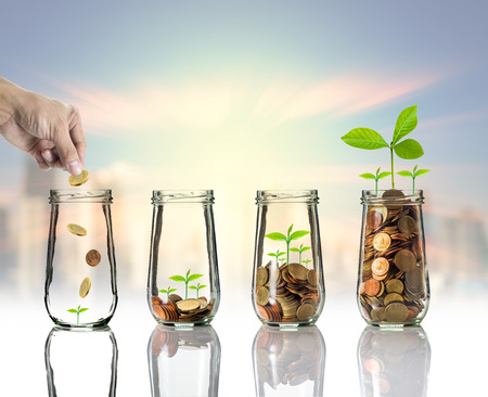 Foto de Hand putting Gold coins and seed in clear bottle on cityscape photo blurred cityscape background,Business investment growth concept - Imagen libre de derechos