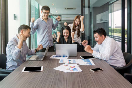 Foto de Group Of AsianBusiness people with casual suit working with happy action and celebrate in the modern Office, people business group concept - Imagen libre de derechos