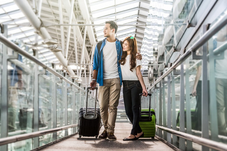 Foto de Asian couple traveler with suitcases at the airport. Lover travel and transportation with technology concept. - Imagen libre de derechos