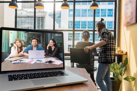 Photo for Computer laptop on the wooden table display Video conferencing With Colleagues and Hipster young couple freelancer when working in the Loft cafe workplace background, entrepreneur business concept - Royalty Free Image