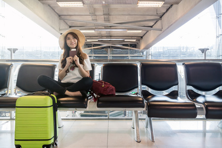 Foto de Happy Asian woman traveler holding the passport with suitcases in modern an airport, travel and transportation with technology concept. - Imagen libre de derechos