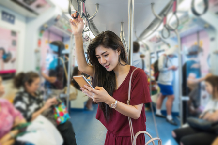 Foto per Asian woman passenger with casual suit using the smart mobile phone in the BTS Skytrain rails or MRT subway for travel in the big city, lifestyle and transportation concept - Immagine Royalty Free
